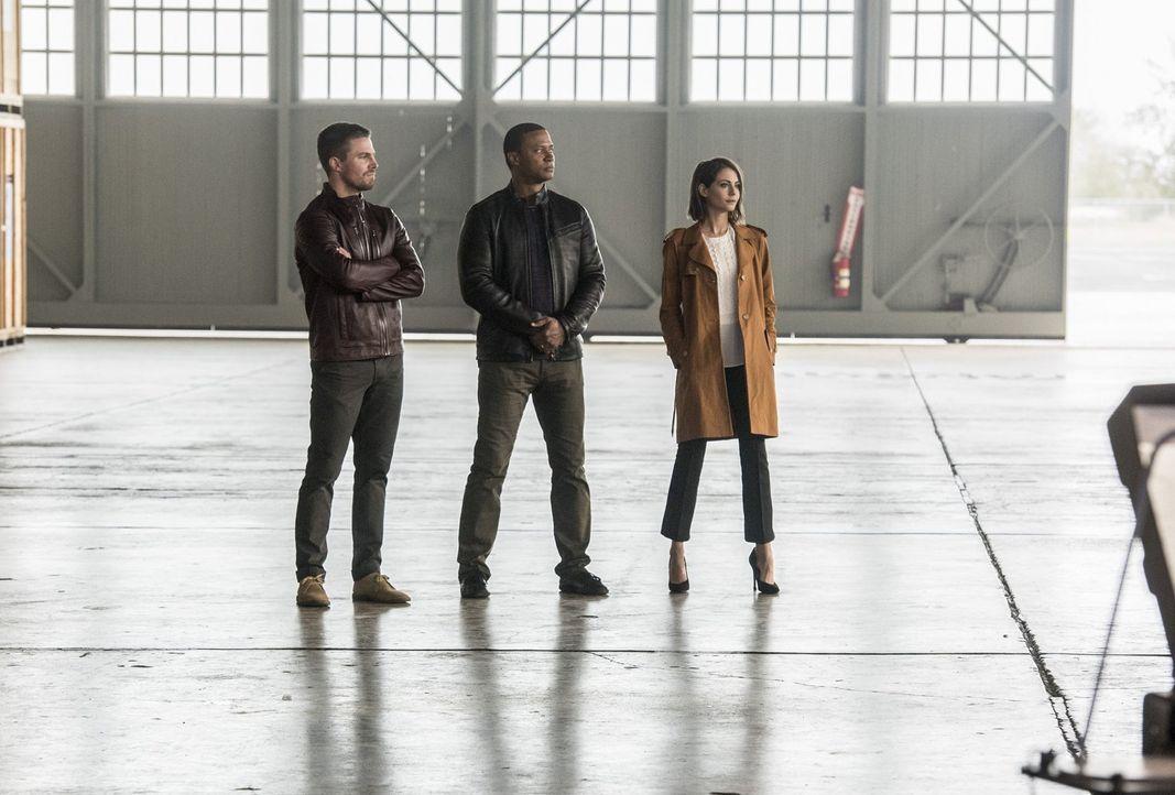 Während sich Oliver (Stephen Amell, l.), John (David Ramsey, M.) und Thea (Willa Holland, r.) auf den Kampf gegen Aliens vorbereiten, erkennt Martin... - Bildquelle: 2016 Warner Bros.