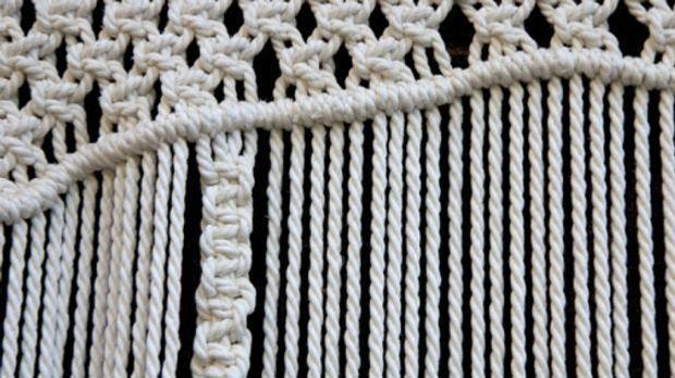 Nahaufnahme von weißen Seilen, die durch Knoten zu einem Muster verknüpft werden
