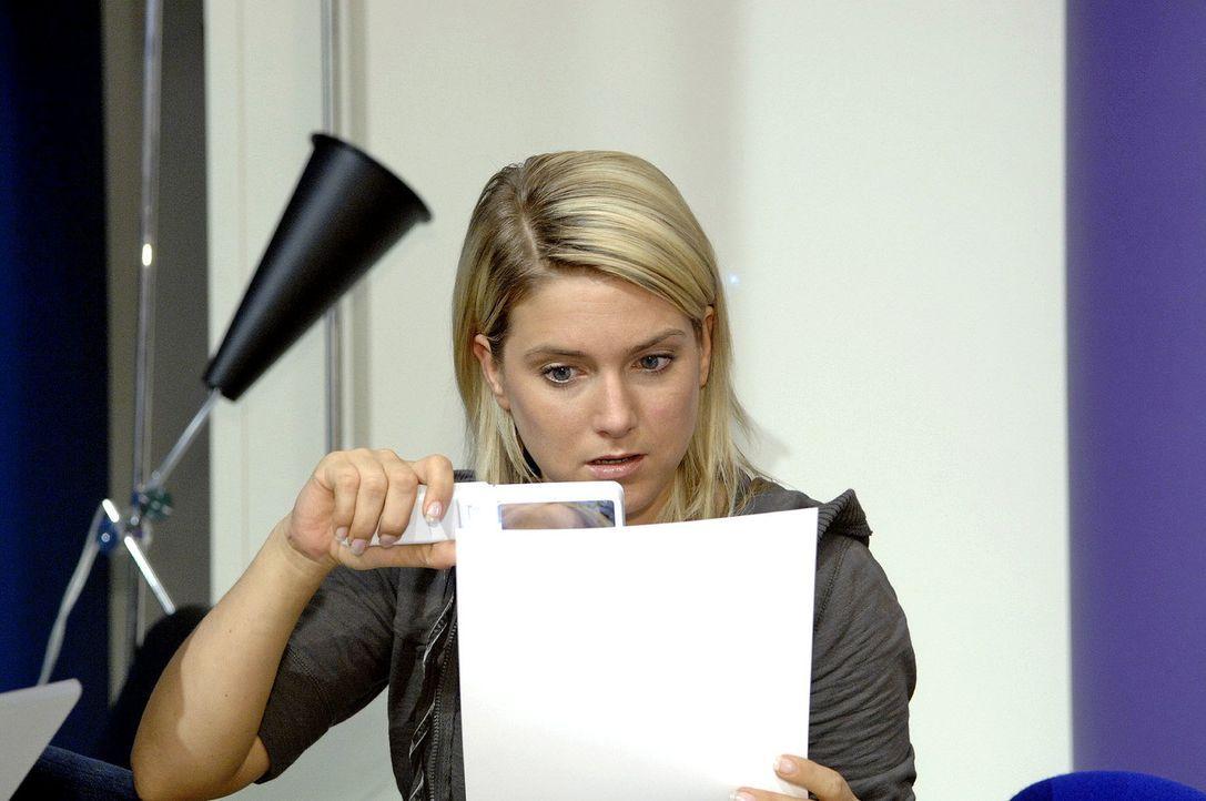 Anna (Jeanette Biedermann) erkennt ihren unbekannten Retter auf den Fotos von dem Straßenshooting wieder. - Bildquelle: Claudius Pflug Sat.1