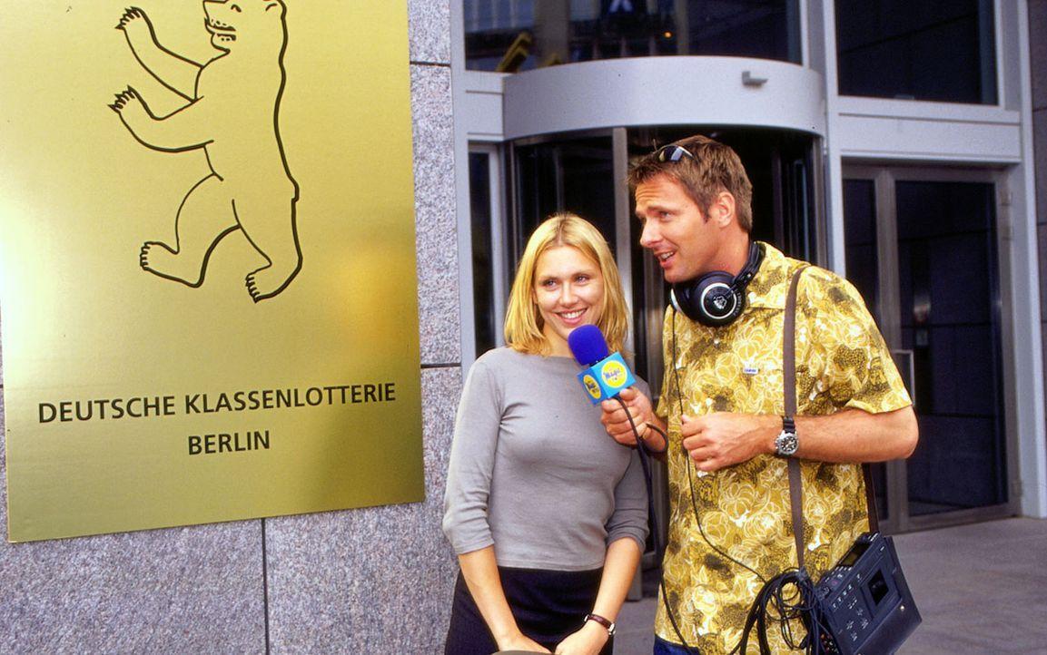 Radioreporter Charly Staudt (Jörg Pilawa, r.) befragt Marie (Gruschenka Stevens, l.) vor dem Gebäude der Deutschen Klassenlotterie, ob sie den Lotto... - Bildquelle: Oliver Ziebe Sat.1