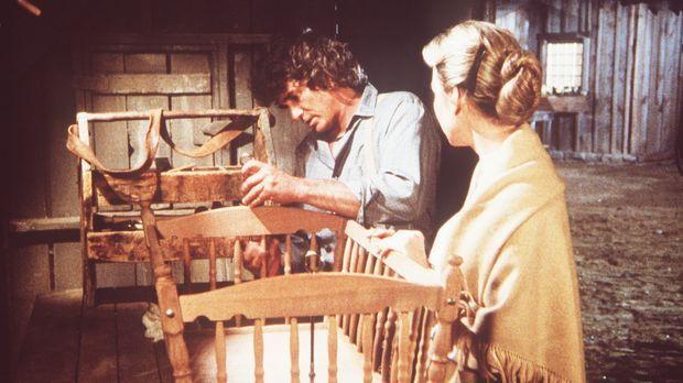 Charles Ingalls (Michael Landon, l.) arbeitet noch spät abends an einer Wiege...