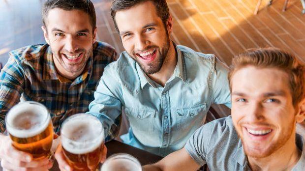 Biertrinker beim Anstoßen mit vollen Biergläsern