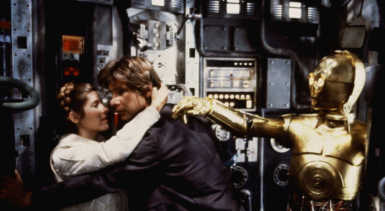 Hemmungslos stört C-3PO (Anthony Daniels, r.) den ungestümen Han Solo (Harrison Ford, M.) bei einem Küsschen mit der Prinzessin (Carrie Fisher, l... - Bildquelle: Lucasfilm LTD. & TM. All Rights Reserved.