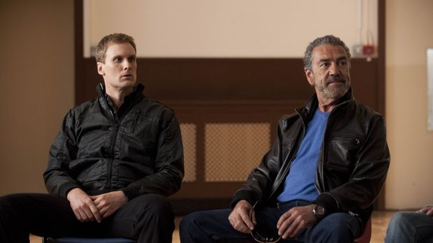 The Examiner (Robert Lindsay) zwingt Tim (Darren Boyd, l.), eine Blutprobe zu...