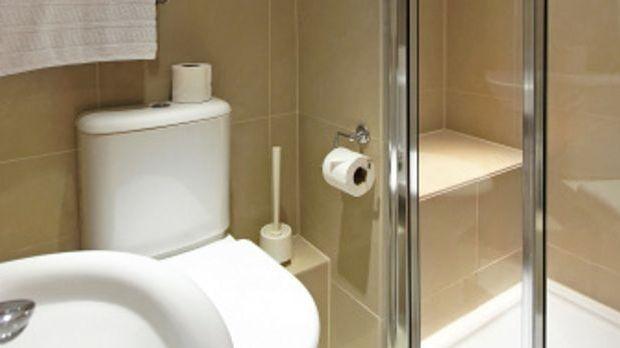 Schmales Badezimmer mit Waschtisch, Toilette, Dusche und Spiegel in Weiß und...