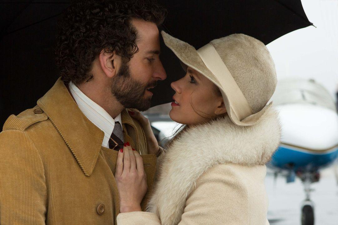 In seiner Verliebtheit ist FBI-Agent Richie DiMaso (Bradley Cooper, l.) nicht klar, dass Sydney (Amy Adams, r.) eine brillante Betrügerin ist, die a... - Bildquelle: TOBIS TFILM