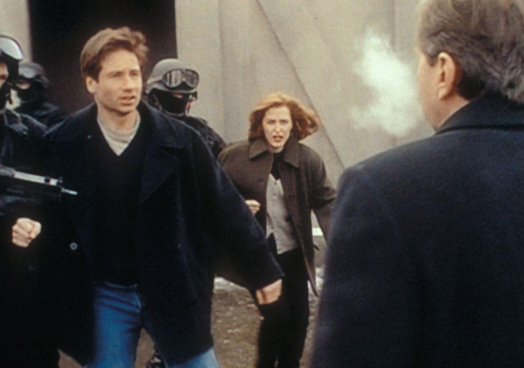 Der geheimnisvolle Raucher (William B. Davis, r.) lässt Mulder (David Duchovny, l.) und Scully (Gillian Anderson, M) aus einem stillgelegten Raketen... - Bildquelle: TM +   2000 Twentieth Century Fox Film Corporation. All Rights Reserved.