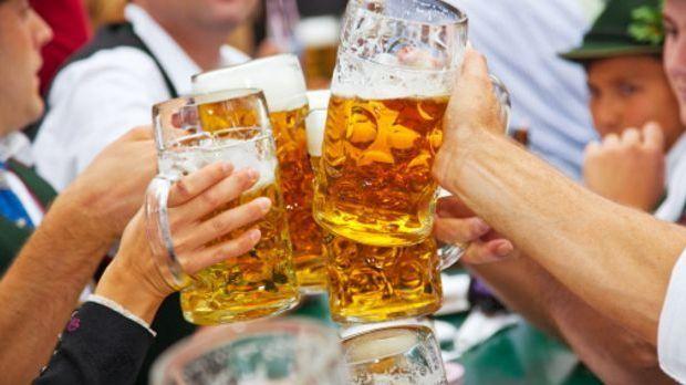 Nahaufnahme von gefüllte Bierkrügen, die zum Anstoßen zusammengeführt werden