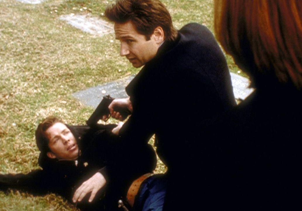 Mulder (David Duchovny, r.) hält den Friedhofsgärtner (Casey C. O'Neill) für den Täter einer Reihe von Morden, bei denen den Opfern das Herz entfern... - Bildquelle: TM +   2000 Twentieth Century Fox Film Corporation. All Rights Reserved.