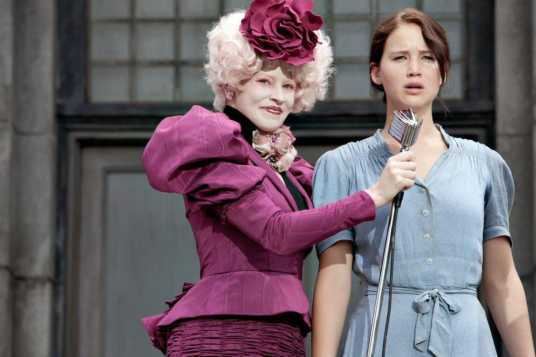 Kaum in der Arena angekommen, wird Katniss (Jennifer Lawrence, r.) von ihrer Betreuerin Effie Trinket (Elizabth Banks, l.) auf die Bühne gezogen. Vo... - Bildquelle: Studiocanal GmbH
