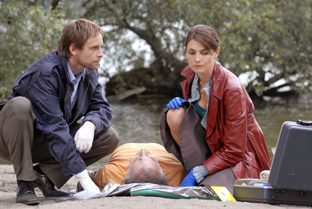 Philip (Julian Weigend, l.) und Stefanie (Nicole Marischka, r.) untersuchen die Leiche Zellers, die Hämatome am Kopf aufweist. Obwohl der Tote wohl... - Bildquelle: Christoph Assmann Sat.1
