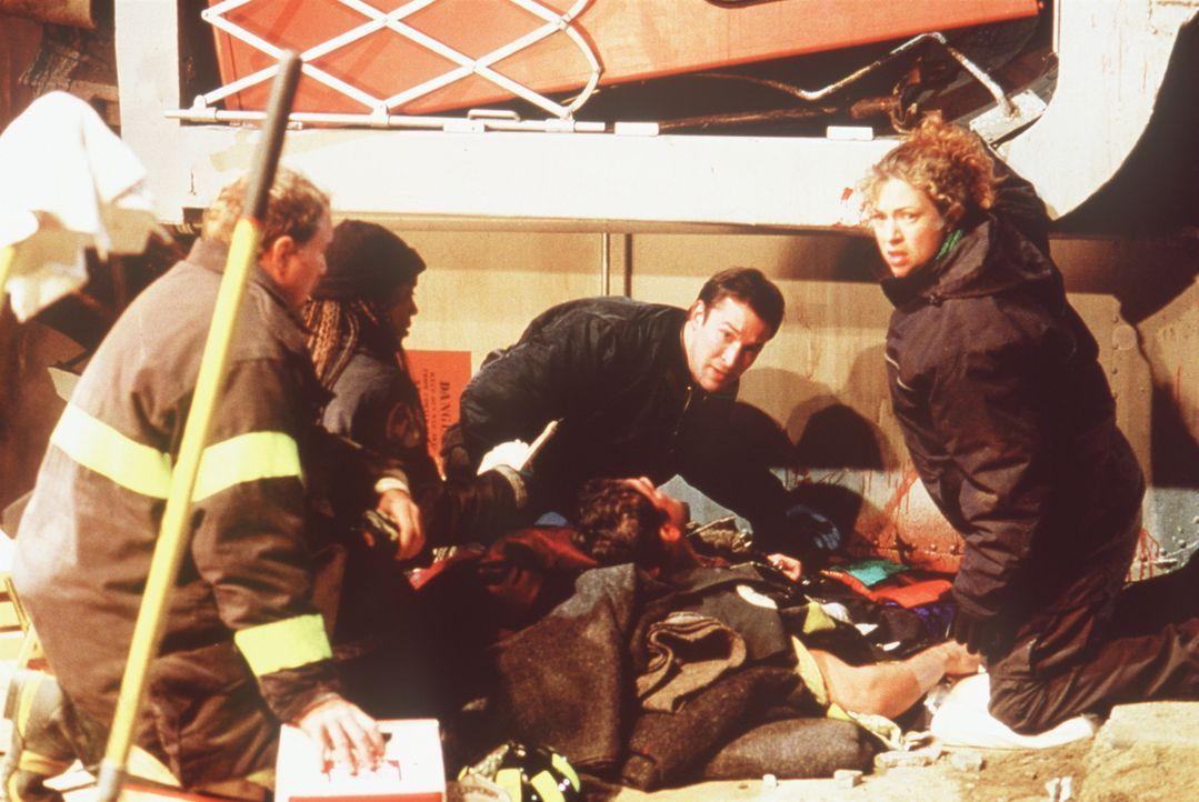 Carter (Noah Wyle, M.) und Corday (Alex Kingston, r.) versuchen, einen Feuerwehrmann, der unter einem umgestürzten Waggon eingeklemmt ist, zu retten. - Bildquelle: TM+  2000 WARNER BROS.