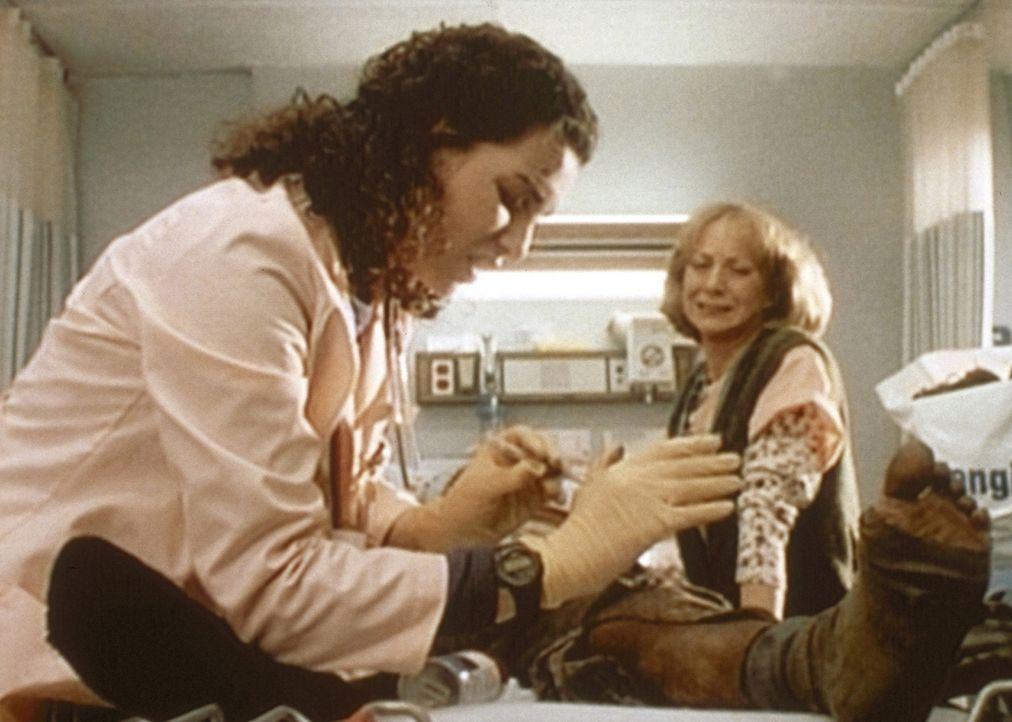 Carol Hathaway (Julianna Margulies, l.) zieht einem eingelieferten Patienten einen Schuh aus und sticht sich dabei an einer dort versteckten Rauschg... - Bildquelle: TM+  WARNER BROS.