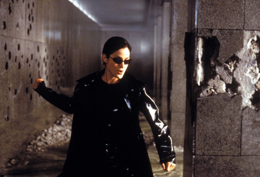 Zusammen mit Neo zerlegt die gefährlich schöne Trinity (Carrie-Anne Moss) die Eingangshalle eines Polizeigebäudes, inklusive Wachpersonal, in sei... - Bildquelle: Warner Bros. Pictures