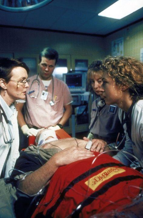 Dr. Weaver (Laura Innes, l.) bemüht sich um eine Patientin, die gearde mit schweren Verletzungen eingeliefert wurde. - Bildquelle: TM+  2000 WARNER BROS.