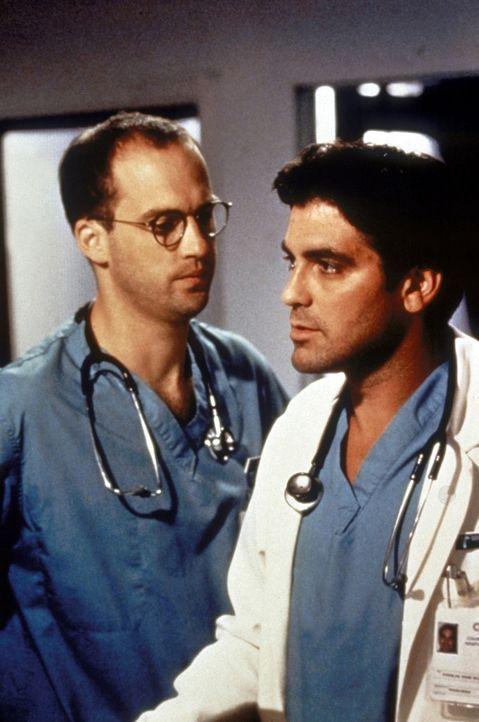 Als Dr. Greene (Anthony Edwards, l.) seinem Kollegen Dr. Ross (George Clooney, r.) mitteilt, dass Carol eingeliefert wurde, ist er besonders betroff... - Bildquelle: TM+  WARNER BROS.