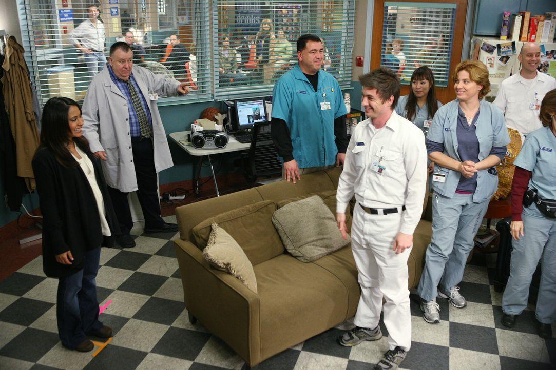Alle Kollegen haben sich versammelt, um Neela (Parminder Nagra, l.) zu verabschieden. Frank (Troy Evans, 2.v.l.) hat sich nicht lumpen lassen und ei... - Bildquelle: Warner Bros. Television