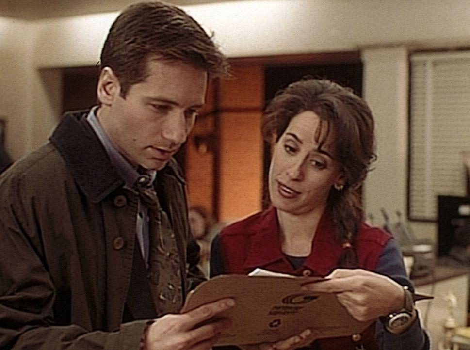 Die Polizistin Lazard (Maggie Wheeler, r.) zeigt Mulder (David Duchovny, l.) den Autopsiebericht eines vor neun Jahren auf ungeklärte Weise ermordet... - Bildquelle: TM +   2000 Twentieth Century Fox Film Corporation. All Rights Reserved.