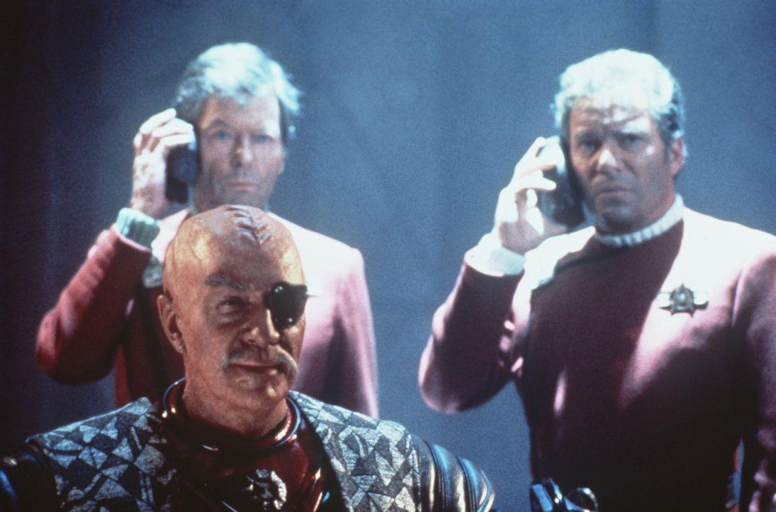 McCoy (DeForest Kelley, hinten l.) und Kirk (William Shatner, hinten r.) erhalten schlechte Nachrichten - doch General Chang (Christopher Plummer, v... - Bildquelle: Paramount Pictures