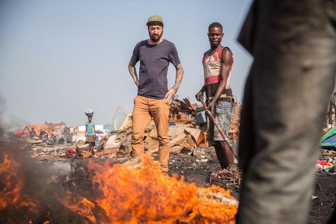 Reporter Oliver Plöger (l.) blickt hinter die Kulissen der Elektroschrottdeponie von Agbogbloshie in Ghana, auf und vor der knapp 50.000 Menschen le... - Bildquelle: ProSieben MAXX