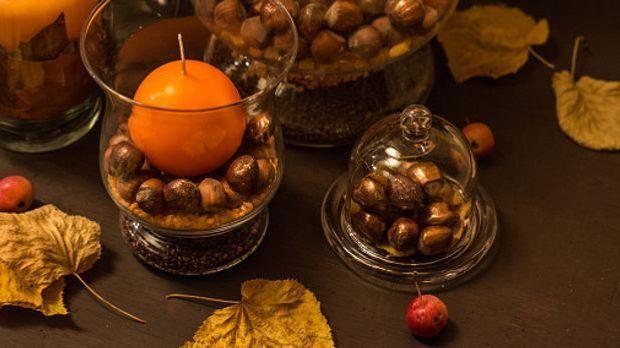 Auf mehreren Eicheln in einem Glas steht eine orangefarbene Kerze