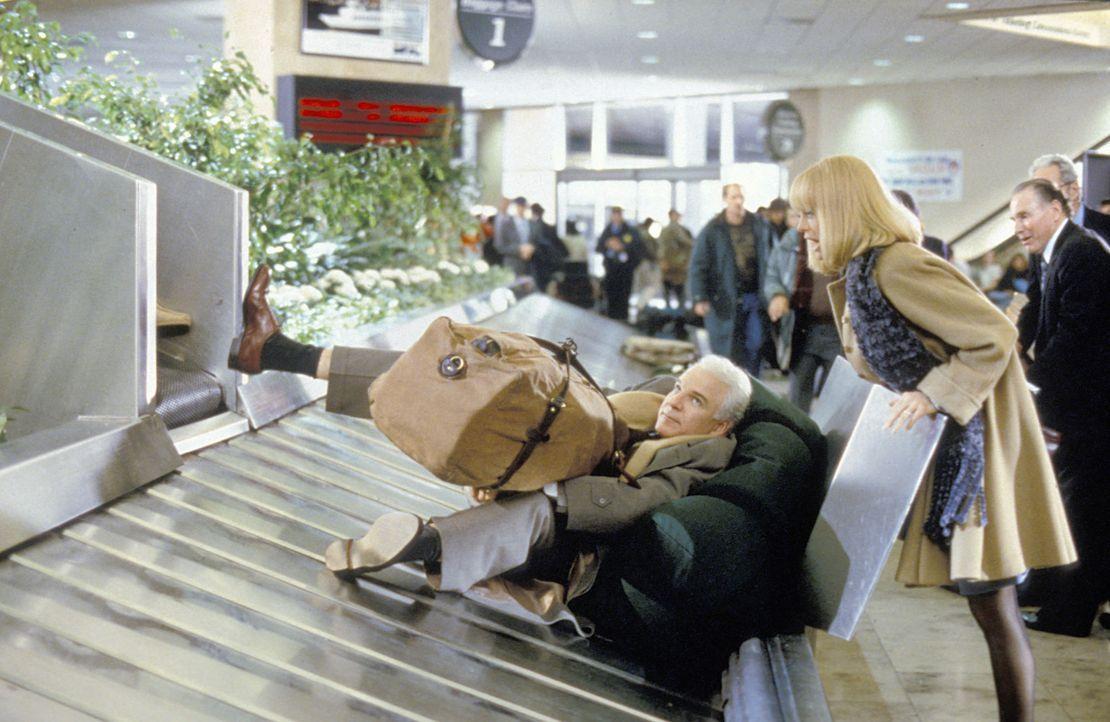 Am Flughafen gelandet, traut Nancy (Goldie Hawn, r.) ihren Augen nicht: Ihr Mann Henry (Steve Martin, l.) liegt inmitten der Gepäckstücke auf dem Förderband ...