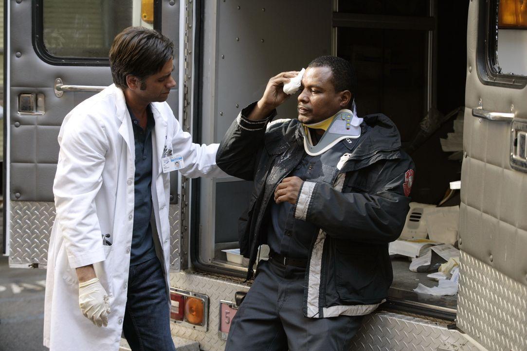 Tony (John Stamos, l.) kümmert sich um Dwight (Montae Russell, r.), der sich bei einem Einsatz verletzt hat ... - Bildquelle: Warner Bros. Television