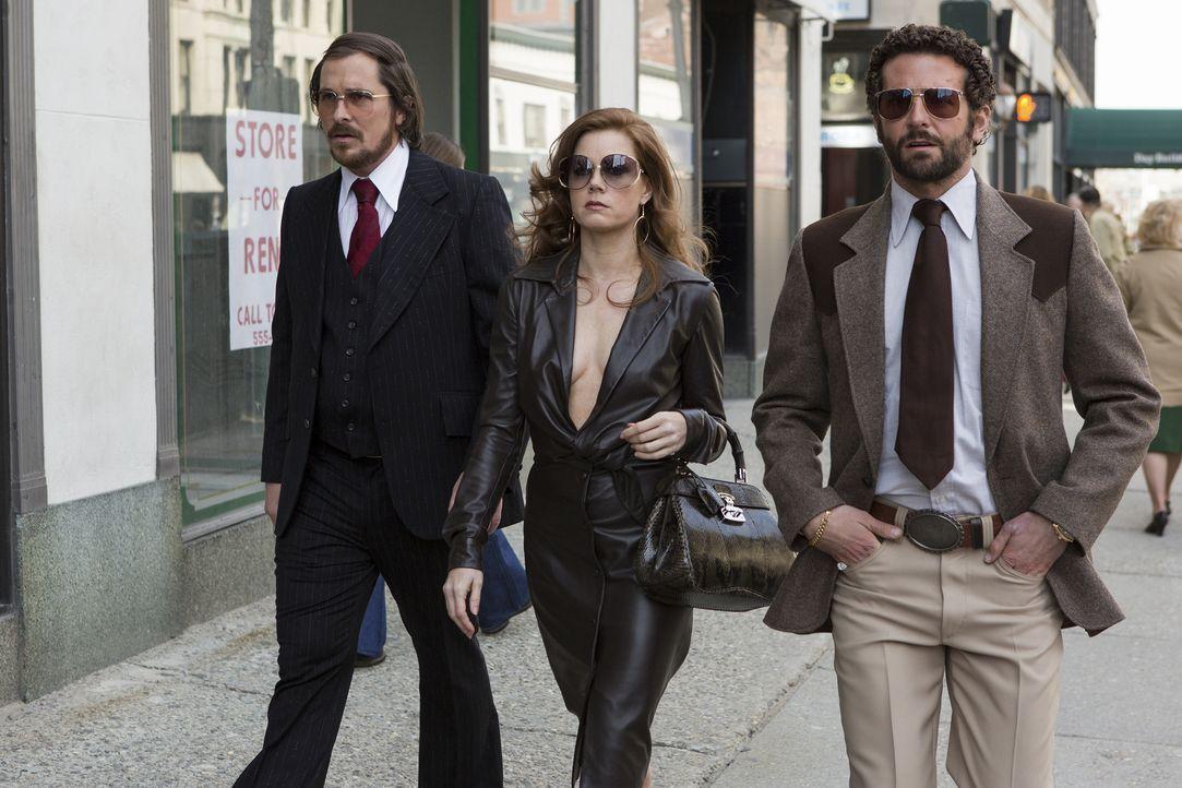 Der gerissene Betrüger Irving Rosenfeld (Christian Bale, l.) versteht sein Handwerk nur allzu gut. Er und seine Freundin Sydney (Amy Adams, M.) sind... - Bildquelle: TOBIS TFILM