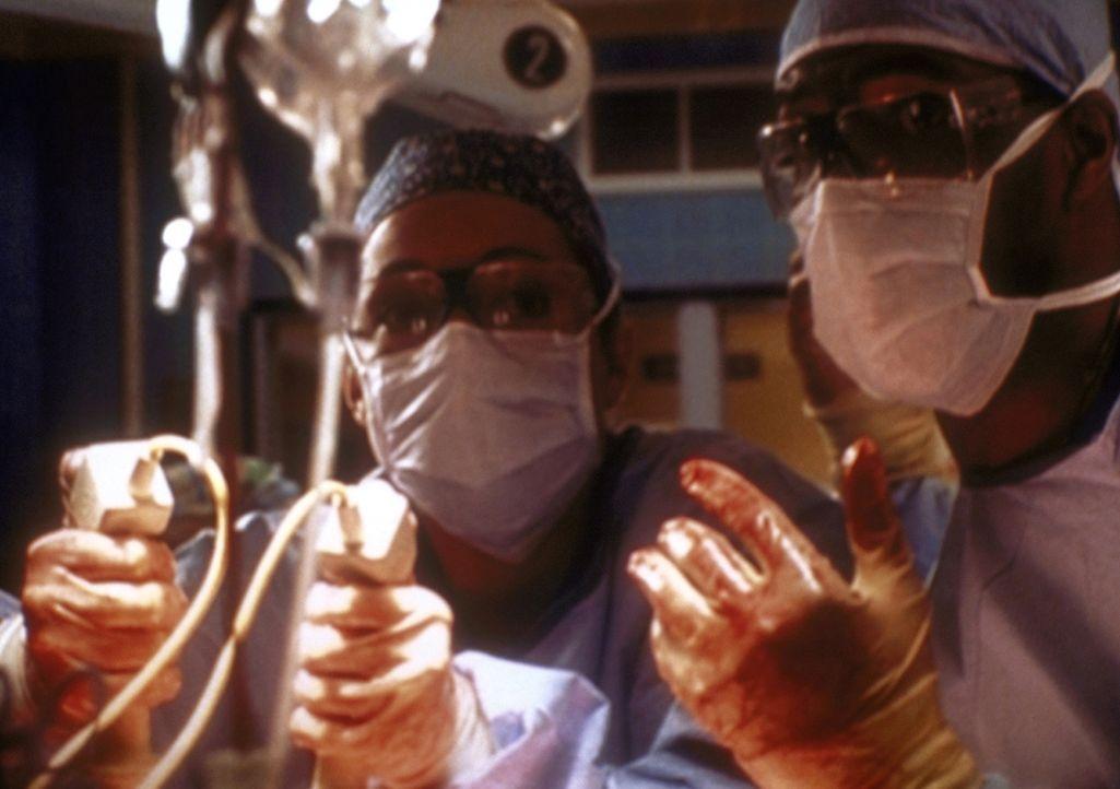 Gemeinsam kämpfen Corday (Alex Kingston, l.) und Benton (Eric La Salle) um das Leben eines kleinen Jungens. - Bildquelle: TM+  2000 WARNER BROS.