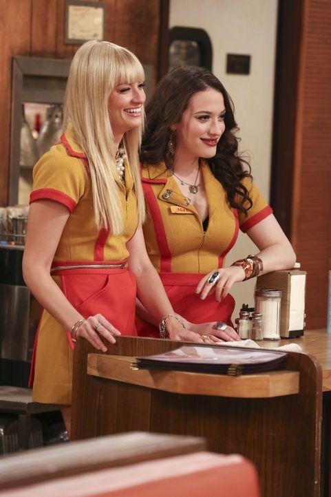 Max (Kat Dennings,r.) und Caroline (Beth Behrs, l.) müssen gute Miene zum bösen Spiel machen. Die Lebensmittelkontrolleurin kommt um sich bei ihne... - Bildquelle: Warner Bros. Television