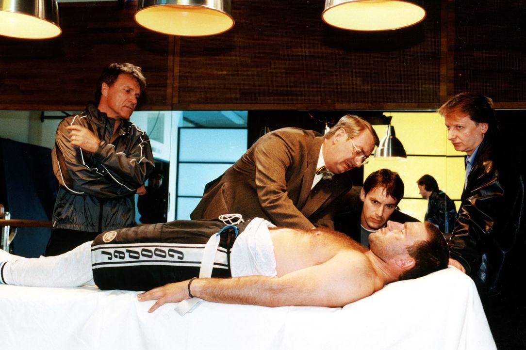 Gerichtsmediziner Dr. Leo Graf (Gerhard Zemann, 2.v.l.) bei der ersten Untersuchung der Leiche des Eishockey-Spielers Pokorny. Kommissar Brandtner (... - Bildquelle: Ali Schafler Sat.1