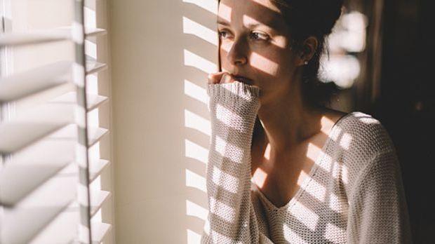 Junge Frau schaut durch das halbgeschlossene Lamellenrollo