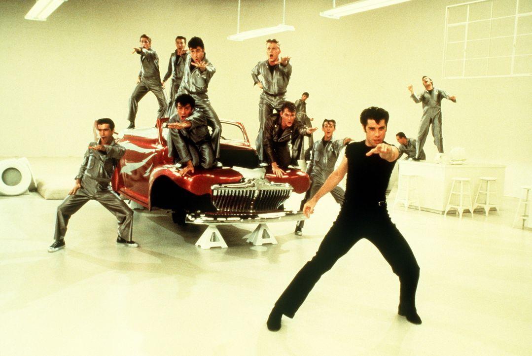 Als Sandy (Olivia Newton-John, l.) überraschend an der High School erscheint, will sich Danny (John Travolta, r.) vor seinen Freunden keine Blöße... - Bildquelle: Paramount Pictures