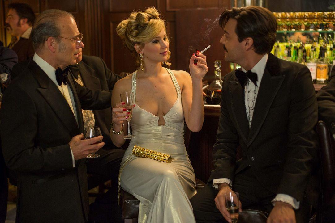 Bringt Irvings unberechenbare und eifersüchtige Ehefrau Rosalyn (Jennifer Lawrence, M.), die sich mit dem Mafioso Peter Musane (Jack Huston, r.) ein... - Bildquelle: TOBIS TFILM