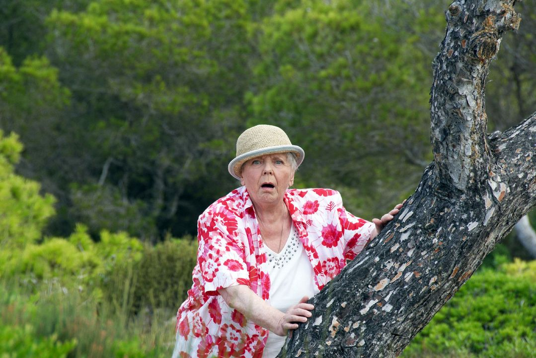 Resi (Ruth Drexel) versteckt sich voller Angst hinter einem Baum, als sie sieht, was mit Hasi geschieht ...