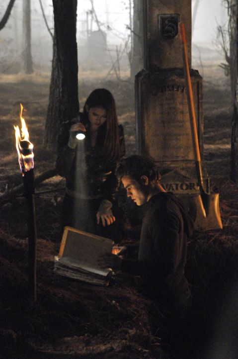 Stefan (Paul Wesley, r.) und Elena (Nina Dobrev, l.) heben in einer Nacht-und-Nebel-Aktion das Grab von Giuseppe Salvatore aus, um an dessen Zauberb... - Bildquelle: Warner Bros. Television