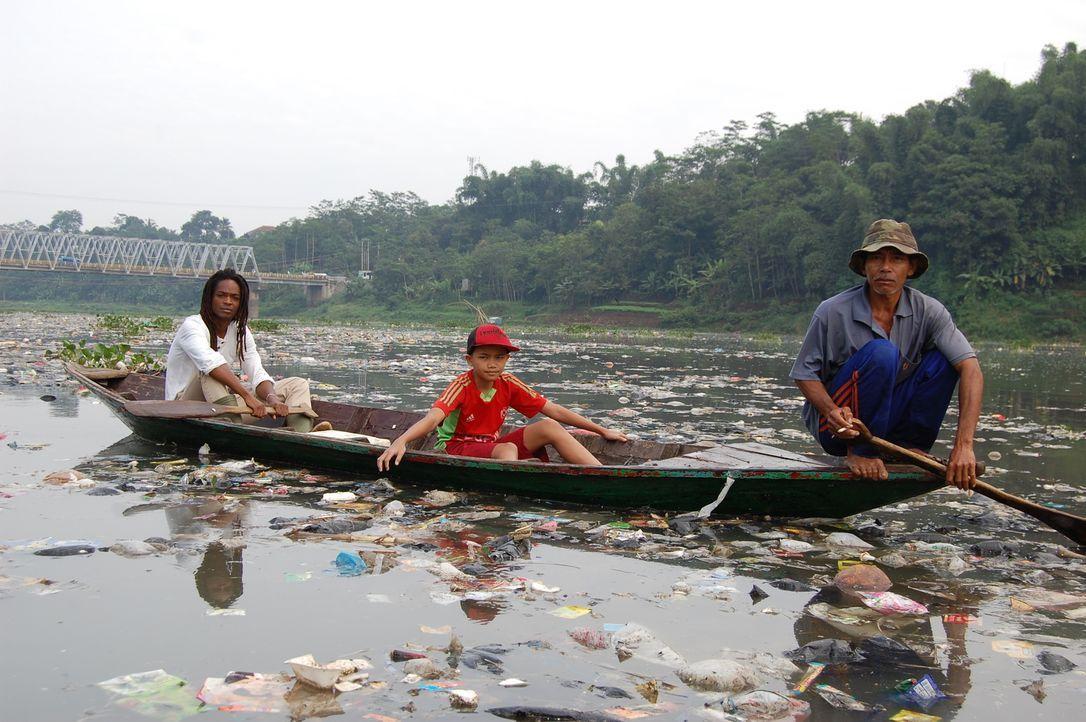 Reporter Seyi Rhodes (l.) begleitet den Fischer Herman (r.) und dessen Sohn Alex (M.) beim Plastikfischen im Citarum ... - Bildquelle: Quicksilver Media 2012