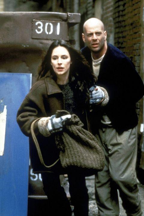 Um die Erde vor dem sicheren Ende zu bewahren, entführt James Cole (Bruce Willis, r.) die Psychiaterin Dr. Kathryn Railly (Madeleine Stowe, l.). Gem...