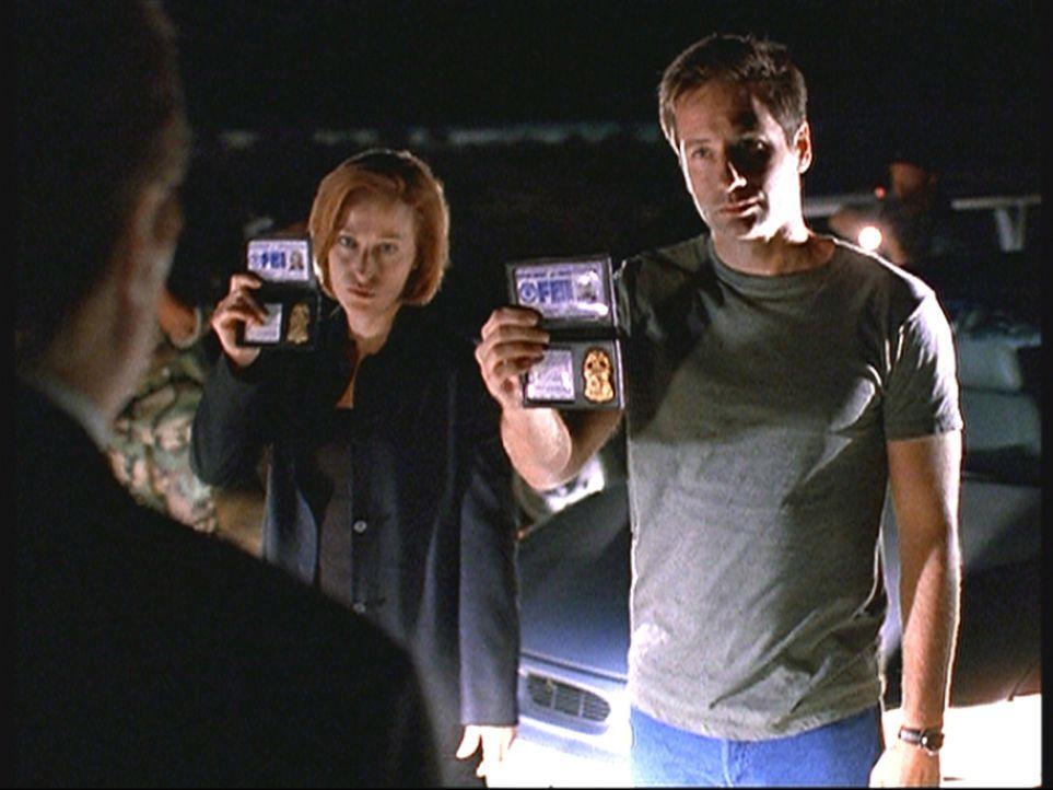 Mulder (David Duchovny, r.) und Scully (Gillian Anderson, M.) werden auf dem Highway 375 in Nevada vom Militär gestoppt und müssen sich ausweisen. - Bildquelle: TM +   2000 Twentieth Century Fox Film Corporation. All Rights Reserved.