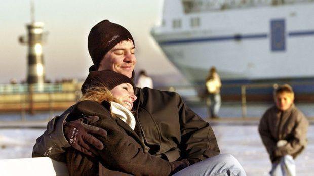 Paar kuschelt auf einer Bank am Hafen