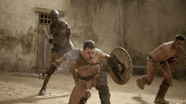 Drago (Peter Mensah, M.) versucht verzweifelt, Spartacus (Andy Whitfield, r.)...
