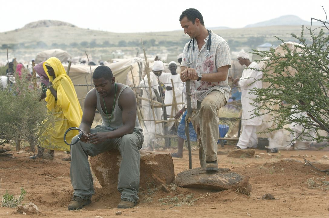 Pratt (Mekhi Phifer, l.) kommt mit dem ganzen Leid, dass sich in Dafur abspielt nicht zurecht. Carter (Noah Wyle, r.) der schon längere Zeit dort tä... - Bildquelle: Warner Bros. Television