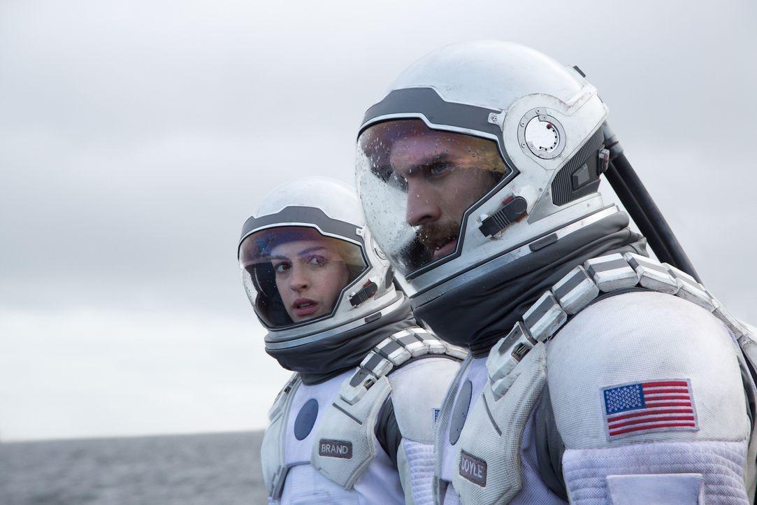 Mit Hilfe von Wurmlöchern begeben sich NASA-Pilot Cooper (Matthew McConaughey, r.), Professor Brands Tochter Amelia (Anne Hathaway, l.) und eine Gru... - Bildquelle: 2014 Warner Bros.