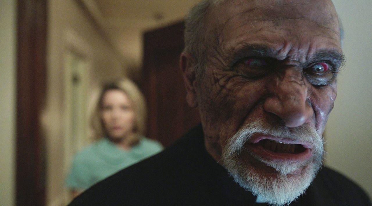 Eigentlich wollte Pater Perez (Tony Amendola) die Puppe Annabelle in die heilige Kirche bringen, um Mia und John zu helfen. Doch Annabelle schreckt... - Bildquelle: 2014 Warner Brothers