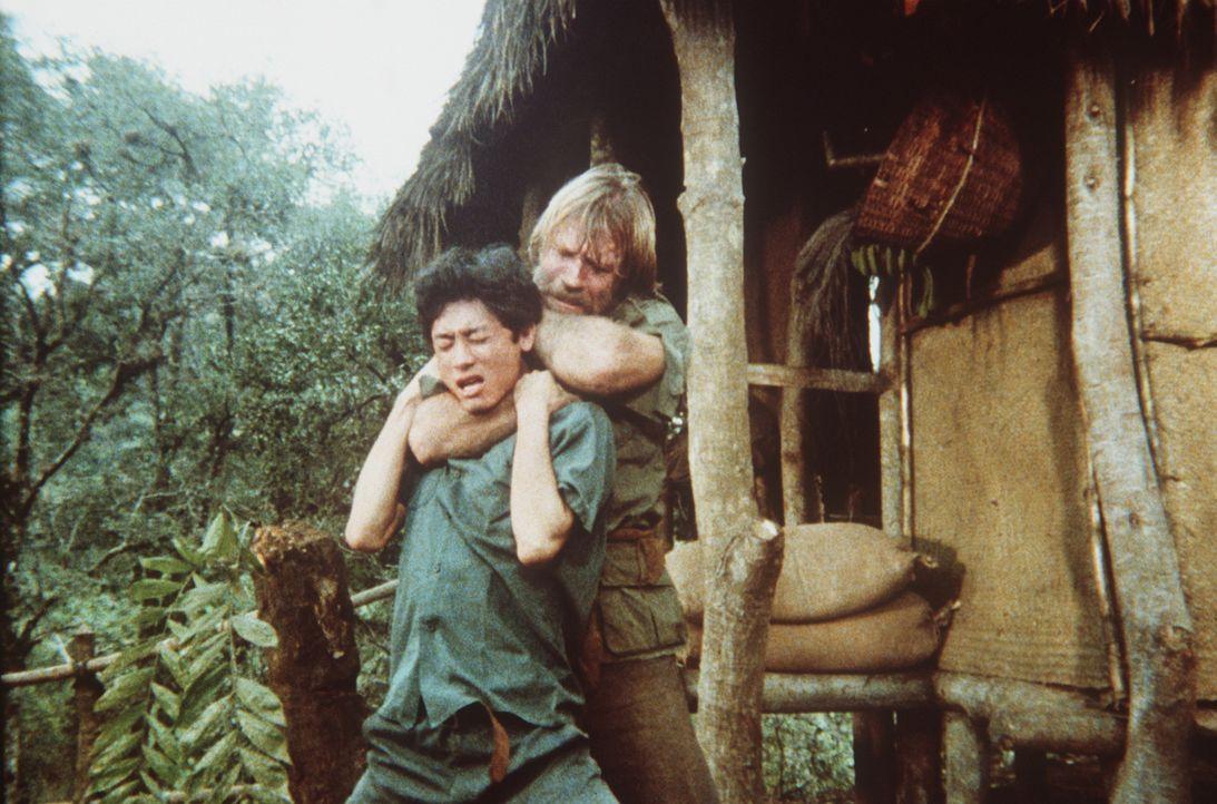 Braddock (Chuck Norris, r.) zwingt einen Wachmann in die Knie und kann aus dem Lager entkommen ... - Bildquelle: Cannon Films