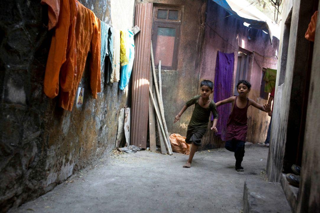 Die beiden Halbwaisen Jamal (Ayush Mahesh Khedeker, l.) und Salim (Azharuddin Mohammed Isamail, r.) kennen sind in den engen Gassen des Slums hervor... - Bildquelle: 2009 PROKINO Filmverleih GmbH