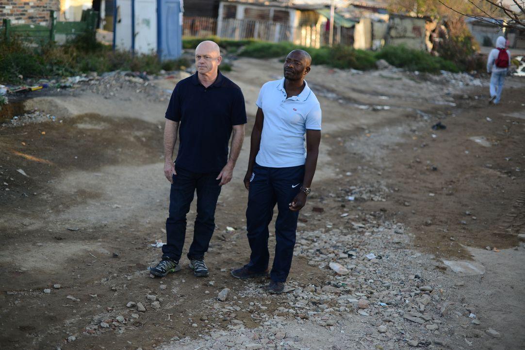 In einem Township vor Johannesburg trifft sich Ross Kemp (l.) mit einem Einheimischen und ist geschockt, welche Informationen dieser ihm über das Th... - Bildquelle: Freshwater Films Ltd 2015