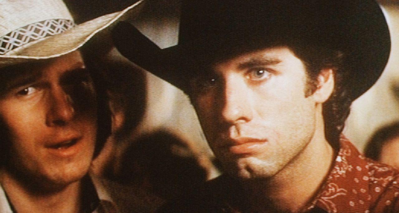 Bud (John Travolta, r.) beobachtet seine Frau beim Flirt mit einem anderen Mann, was dem Macho ganz und gar nicht gefällt ...