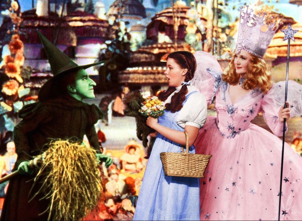 Die böse Hexe des Westens (Margaret Hamilton, l.) möchte die magischen Schuhe ihrer Schwester herbeizaubern, doch die Hexe Glinda (Billie Burke, r.)... - Bildquelle: Warner Bros.