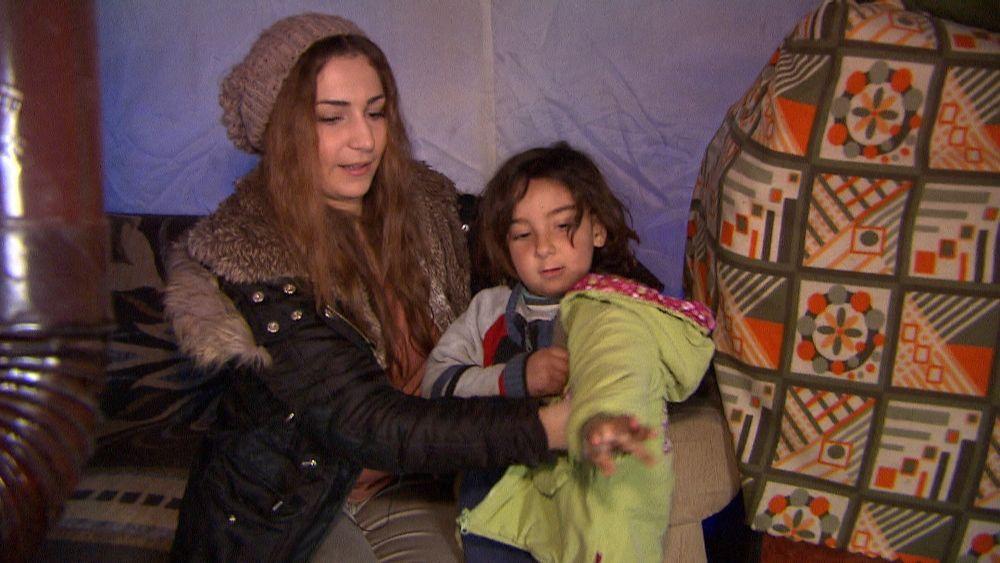 Yasmin schenkt einem Kind eine warme WInterjacke